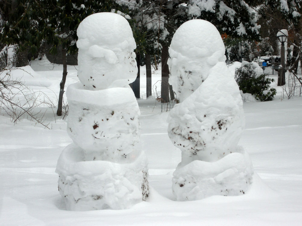 Snowmen with faces in front yard