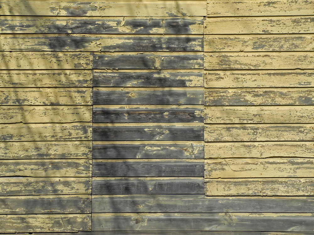 Side of yellow wooden building on Goodman Street in Rochester, New York
