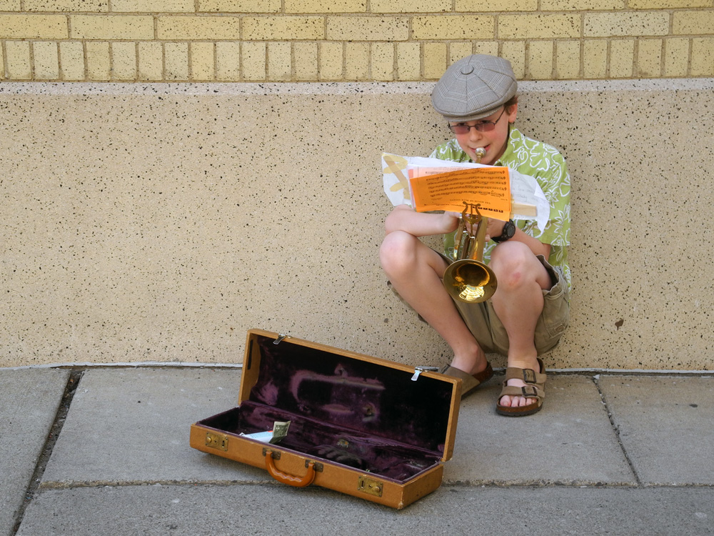 Kid trumpeter in the alley behind the Eastman Theater in Rochester, New York