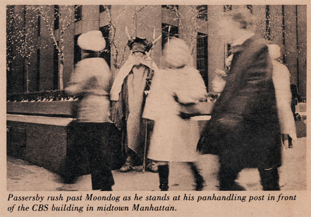 Passersby rush past Moondog as he stands at his panhandling post in front of the CBS building in Midtown Manhattan