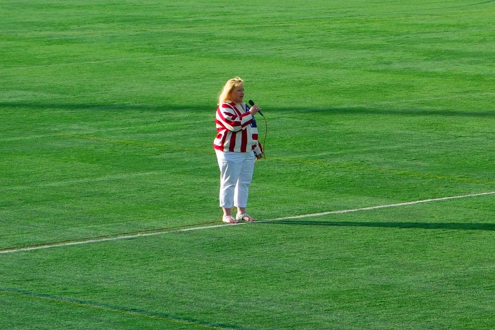 Woman singing national anthem at Flash soccer game