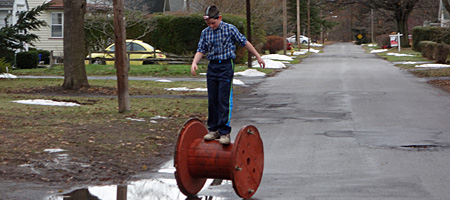 Kid on utility company spool, Rochester, New York