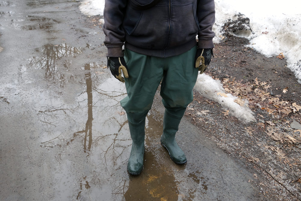 Jared standing in street with his waders on.