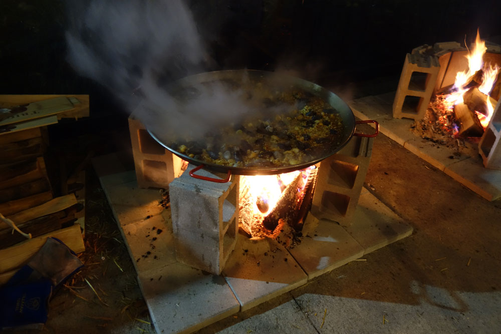 Paella cooking over an open fire at Wegman's Next Door restaurant