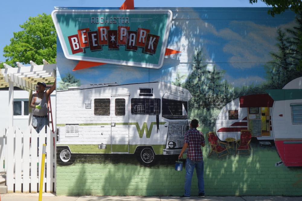 Mural painter working front of Rochester Beer Garden