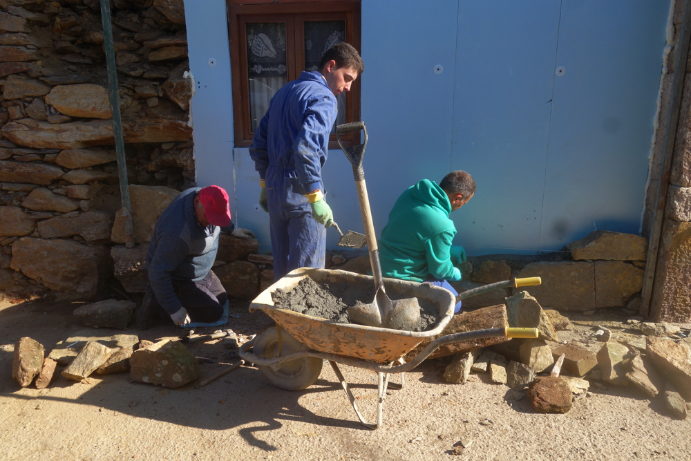 Stone masons restoring an old house in a small town along the Camino de Santiago