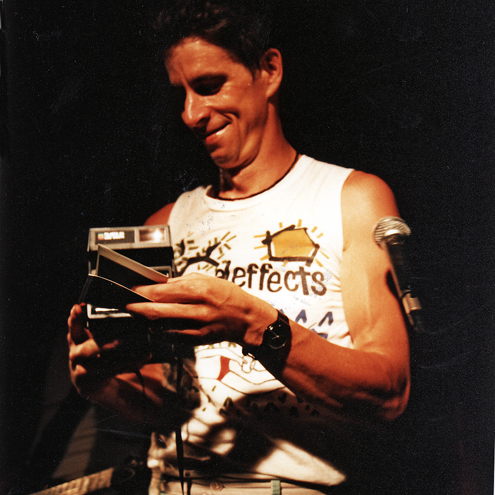 Paul Dodd with Poloroid camera, taking pictures from the stage at Scorgies in Rochester, New York.