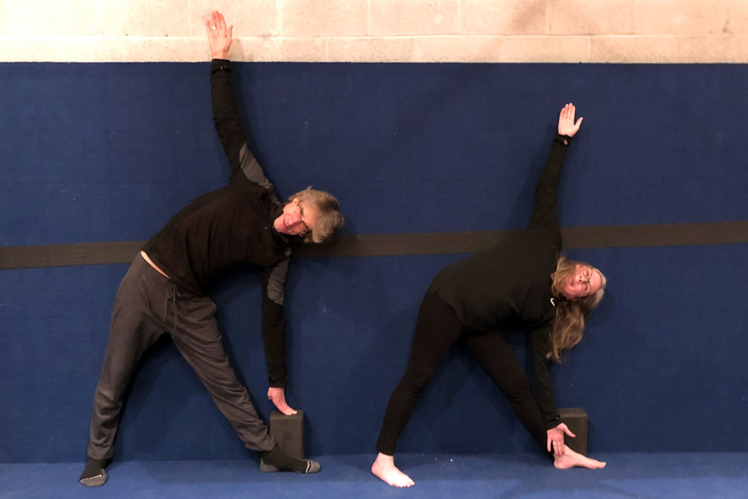 Paul and Peggi doing triangle pose against the wall in yoga class