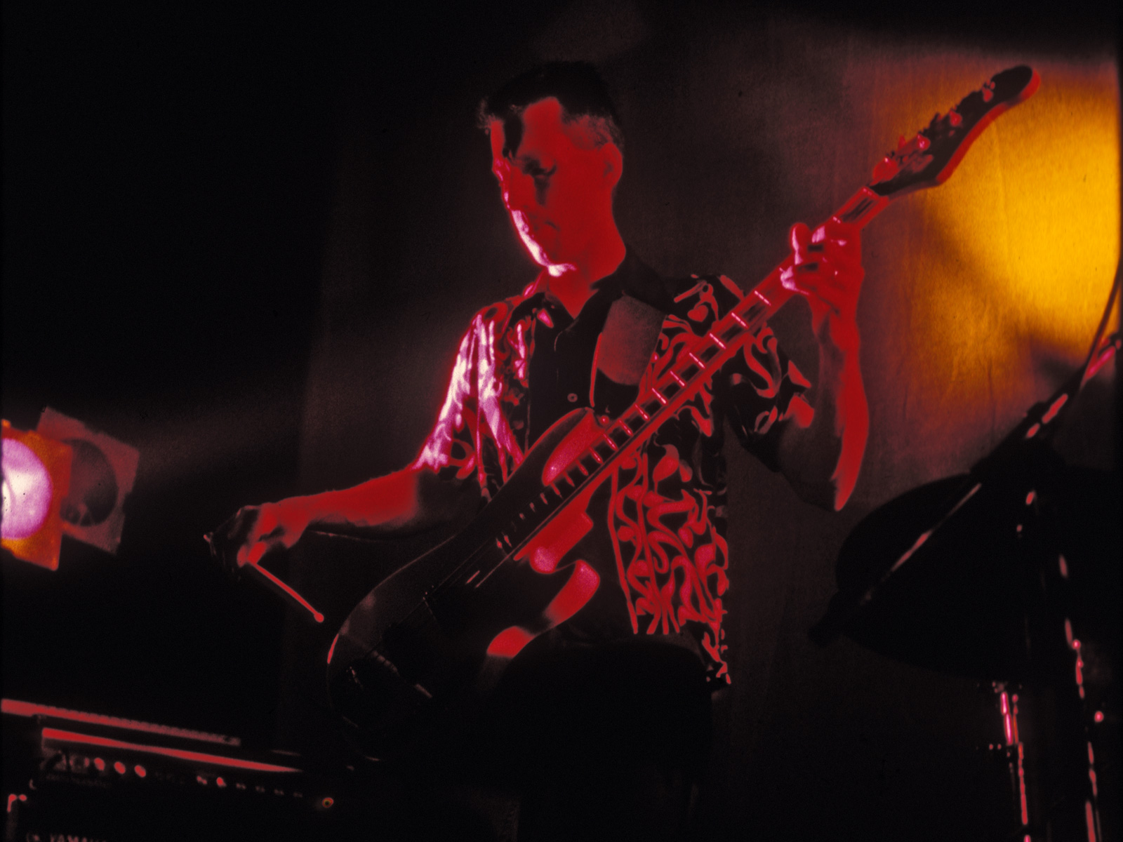 Bernie Heveron playing bass guitar with drum stick with Personal Effects.