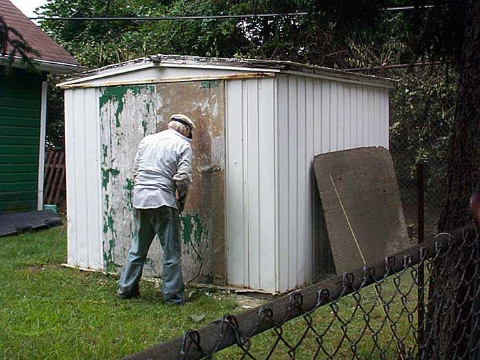 Sparky takes an electric sander to the shed door.