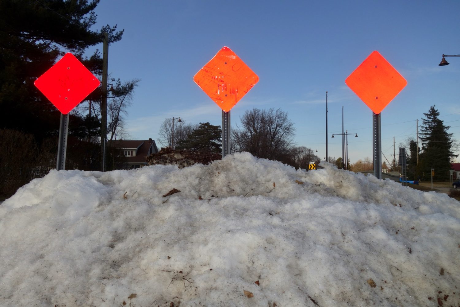 Three orange signs along Sea Breeze Drive at dusk.