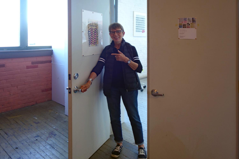 """Anne Havens in doorway of Colleen Buzzard's Studio with her """"Seeing Is Believing"""" piece on the door."""