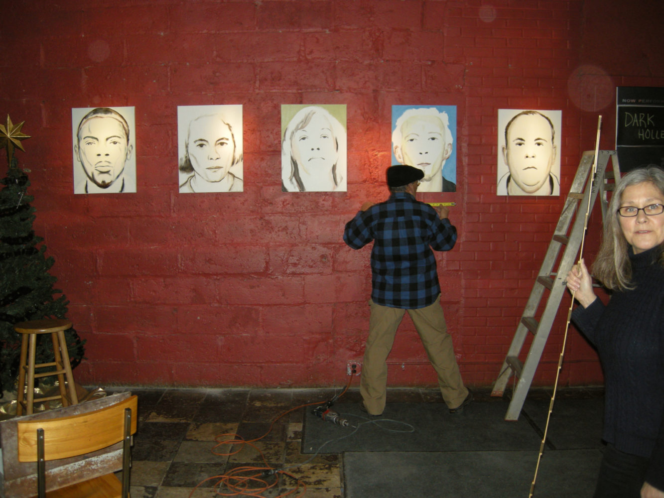 "Peter Monacelli installing Paul Dodd ""Local Crime Faces 2009"" at Little Theatre Café 2009"