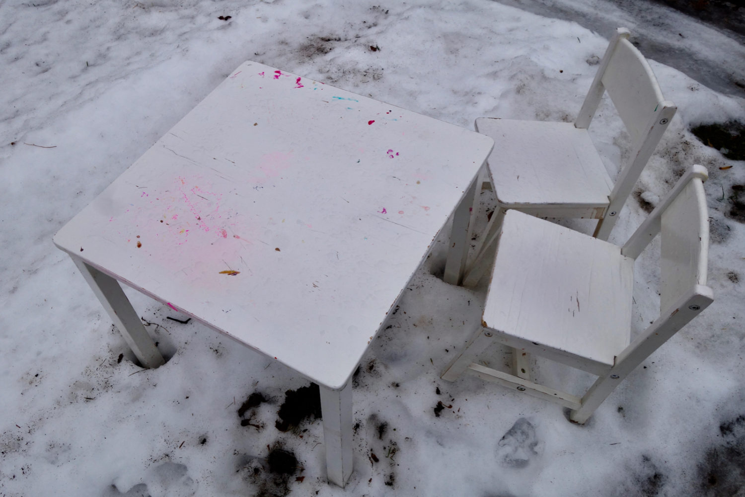 Small white table and chairs by the street in the snow