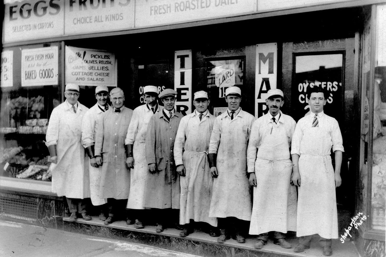 "Tierney Market 1930. Owners, Ray Tierney, Art Tierney, Joe Tierney, Joe Switzer, George Fichtner, Hugh Lurtzinger, John Fichtner, Gus Waggenhauser, and ""Little Angelo."""