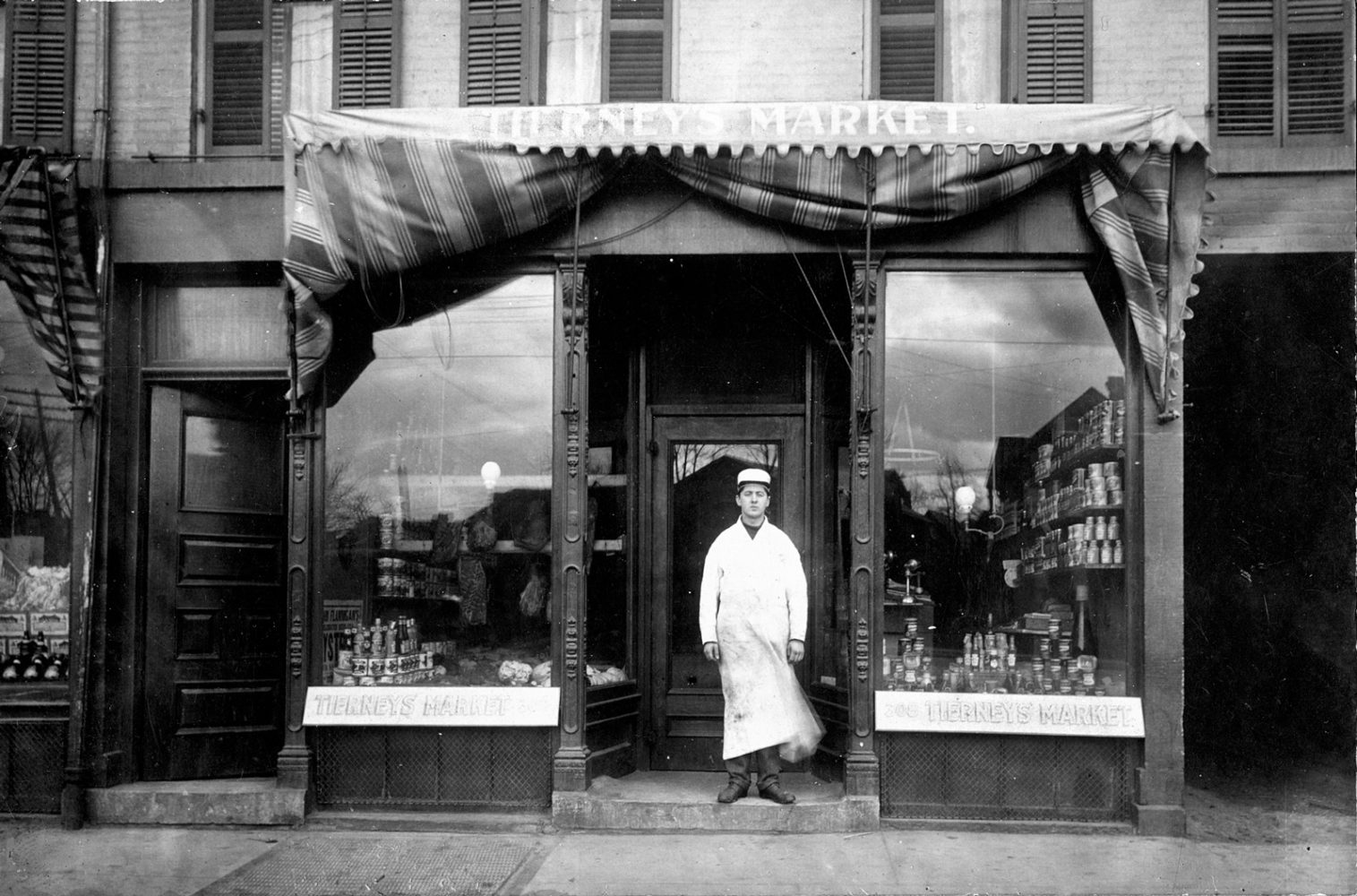 Ray Tierney in front of his first store 312 North Street in Rochester, New York 1906. The livery way which he later converted to rental space for a restaurant is shown to the right.