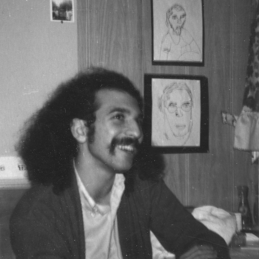 Jeff smiling at the kitchen table. Steve Hoy drawings of Dave and Paul are on the wall behind him.