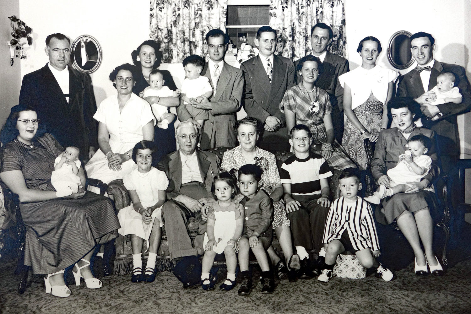 Back row, left to right: Jerry Austin, Rita (Tierney) Austin, Isabel (Tierney)Williams with Greg Williams in her arms, Jack Williams with Chris Williams in his arms, Ray Tierney Jr, Ann Tierney, Ed Kolb, Mary (Tierney) Dodd, Leo Dodd with Paul Dodd in his arms, Front row: Martha (Tierney) Kolb with Nancy Kolb in her arms, Mary Austin, Ray Tierney Sr. Mary (Miami) Tierney with Kathleen Kolb and Jim Austin sitting in front of her, Dick Austin, Ray Tierney III, Rita (Ritzenthaler) Tierney with Debby Tierney in her arms.
