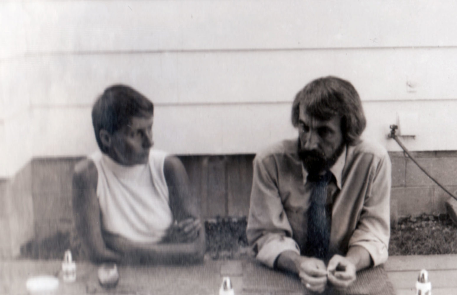 Mary and Leo Dodd sitting at table in our backyard 1969