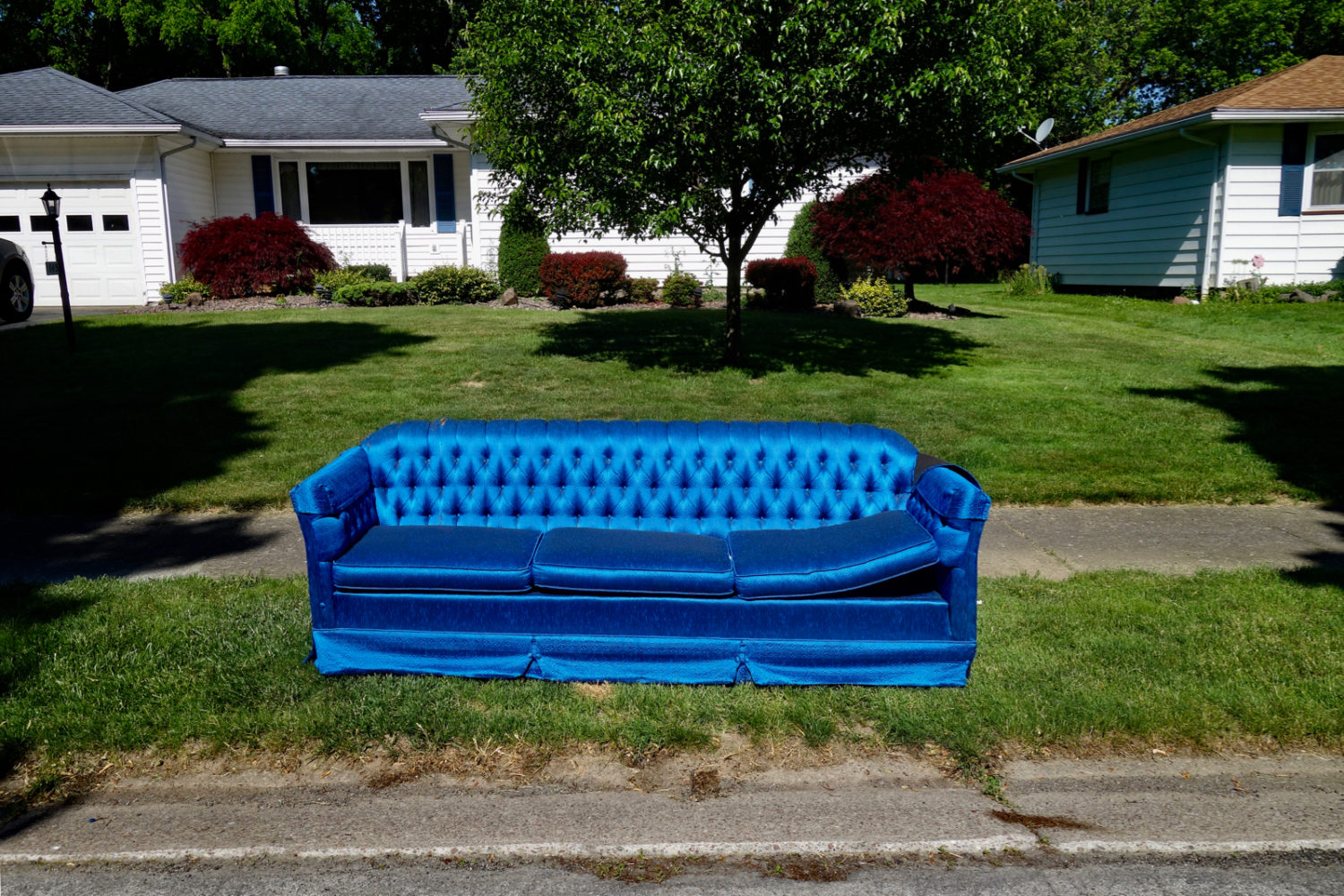 Bright blue couch at curb on side street off Wahl Road, Rochester NY.