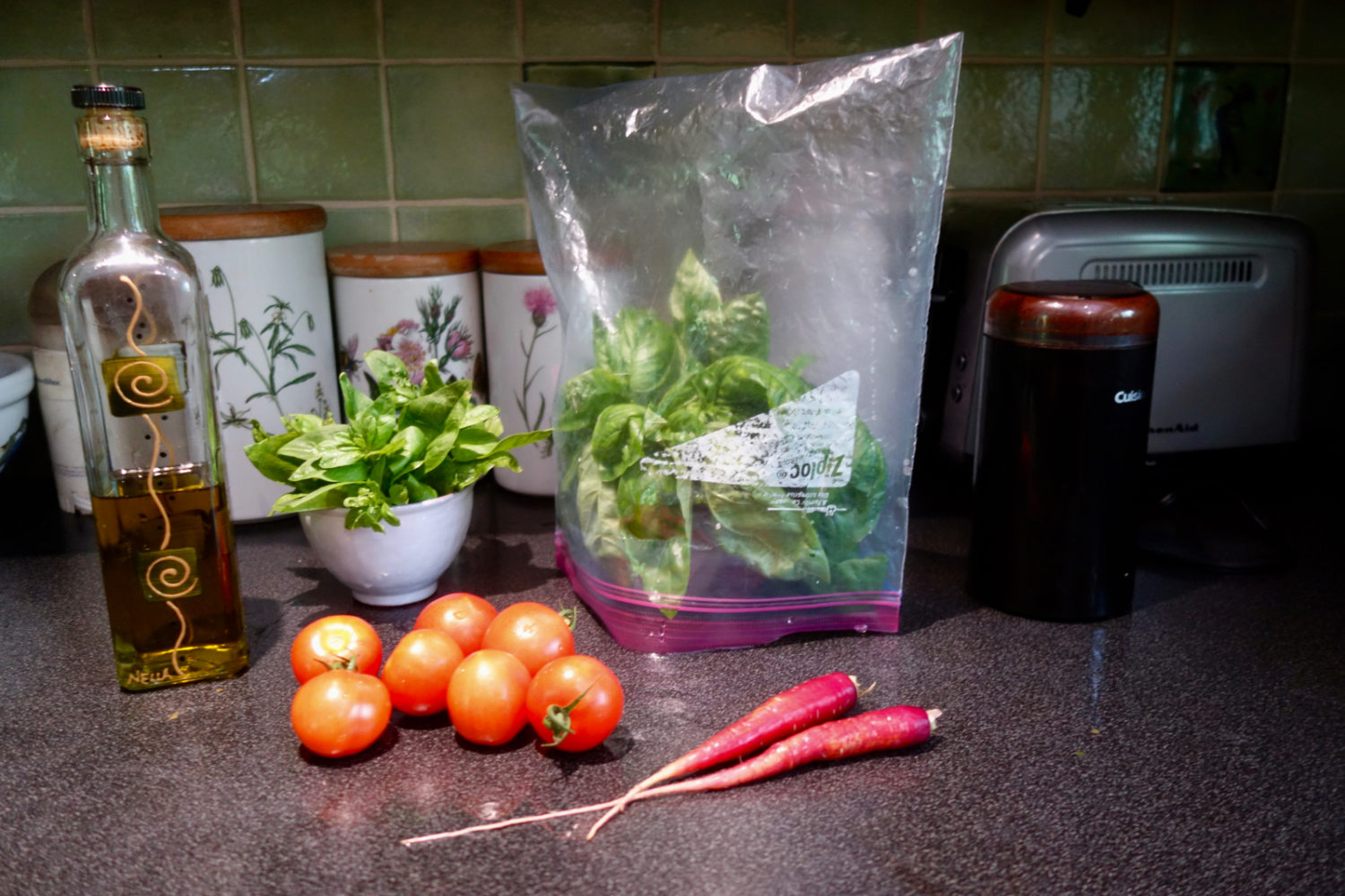 Olive oil, basil, basil in a plastic bag tent and carrots from the garden