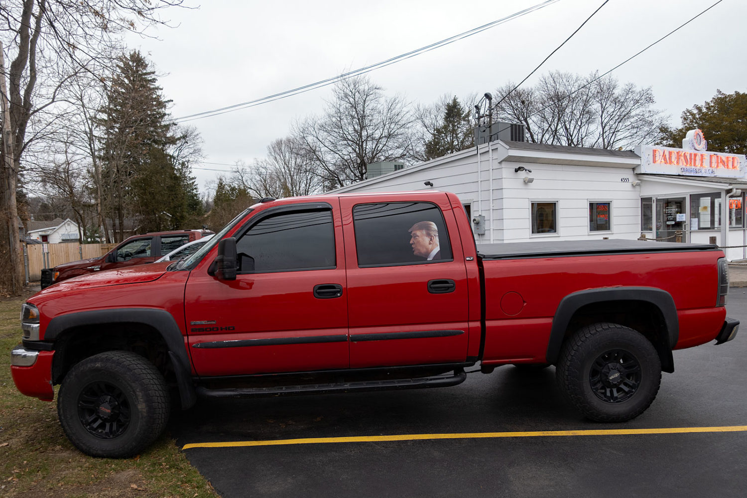 Picture of Trump in the back seat of a red pickup truck at Parkside Diner