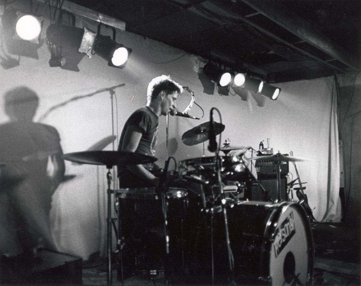 Paul playing drums with vocal mic at Scorgies