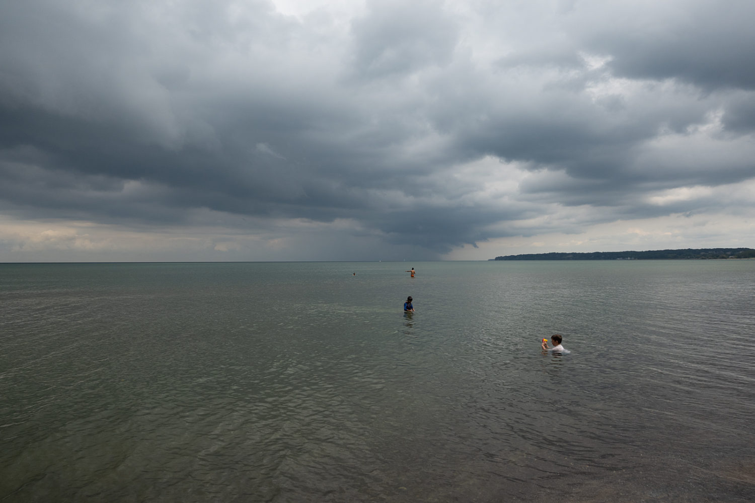Bathers in Lake Ontario with dark clouds