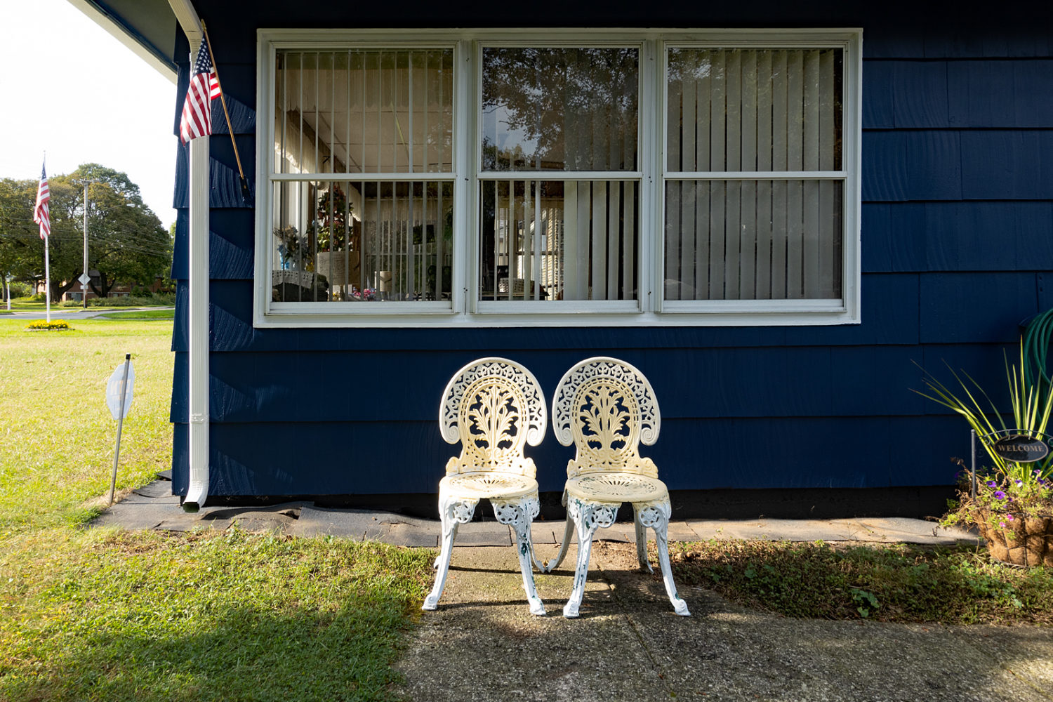 Yellow and white wrought iron chairs in front of house on Culver Road